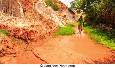 Tourist Walks Barefoot Photos in Fairy-Stream Shallow Water...