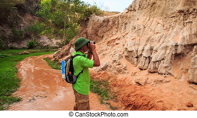 Camera Moves to Tourist Walking along Narrow Fairy Stream