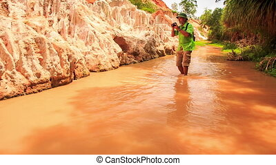 Tourist Walks Barefoot Photos in Fairy-Stream Shallow Water