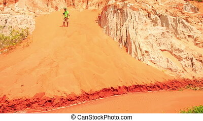 Tourist Climbs up Fairy-Stream Sandy Slope Photos - tourist...