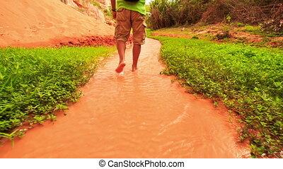 Tourist Walks Barefoot along Fairy-Stream by Rocks Grass -...