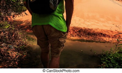 Tourist Barefoot Crosses Stream to Sandy Bank in Park -...