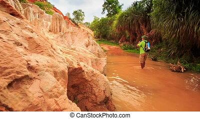 Camera Moves to Tourist Walking along Narrow Fairy Stream -...