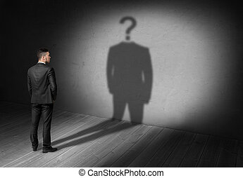 Businessman looking at question mark instead of head his...