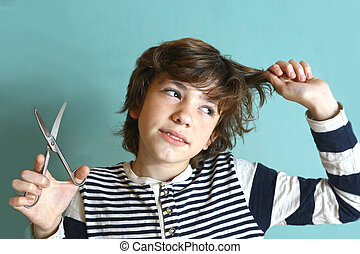 boy with scissors try to cut his hair - preteen handsome boy...
