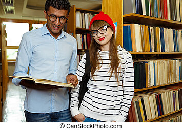 Young student couple choosing books in the library