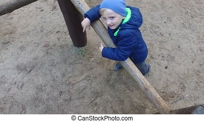 Boy child blonde is engaged in the wooden logs. Little boy playing on the playground.
