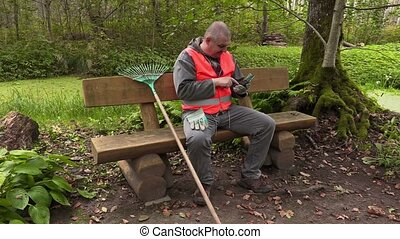 Park  employee sitting on bench and using tablet PC