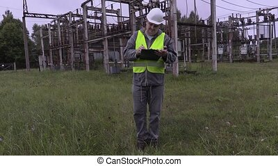 Electrician engineer writing documentation and walking in...