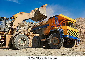Wheel loader loading ore into dump truck at opencast - Heavy...