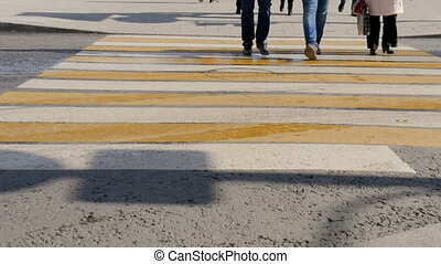 People cross the road at a pedestrian crossing - People...