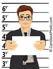 Arrested businessman posing for mugshot holding a signboard...