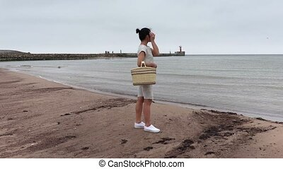 Woman with basket waiting near sea
