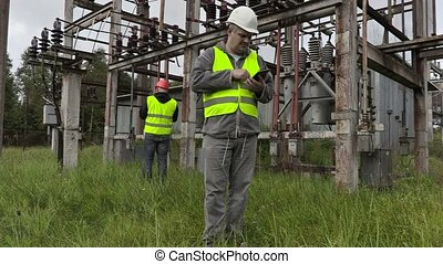 Disappointed electrician using tablet PC in substation