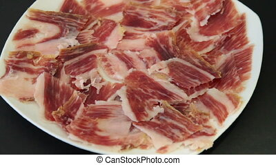 jabugo ham plate - Man right hand picks serrano ham from a...