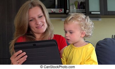 mother with little daughter start video conversation with father on tablet