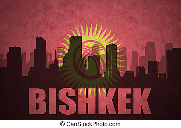 abstract silhouette of the city with text Bishkek at the vintage kyrgyzstan flag background