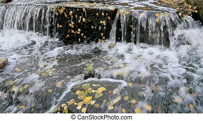 A small waterfall in the park in autumn.
