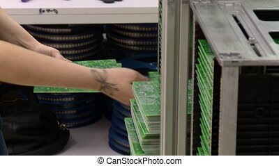 worker manually sorting circuit boards closeup
