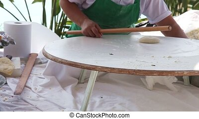 Traditional Turkish pastry - Woman using a rolling pin to...