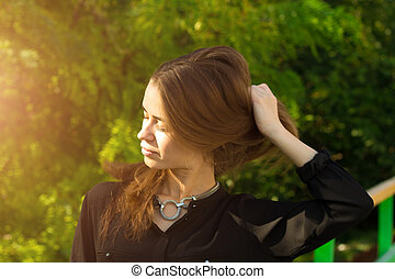 Young woman touching her hair - Young pretty woman in black...