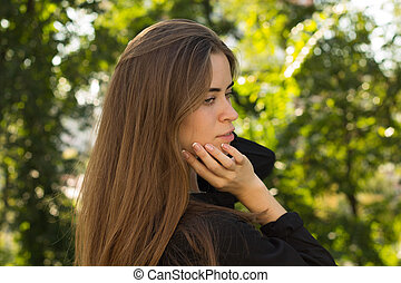 Young woman standing back on the background of trees - Young...