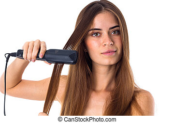 Woman using hair straightener - Young beautiful woman with...
