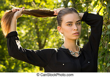 Young woman fixing her hair - Young adoreable woman in black...