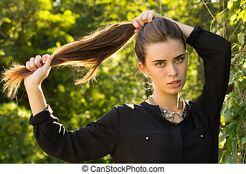 Young woman fixing her hair - Young serious woman in black...
