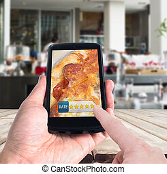 Online rating concept with mobile device against restaurant...