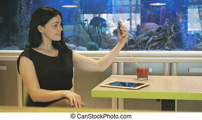 Girl sitting at a cafe and drinking a juice