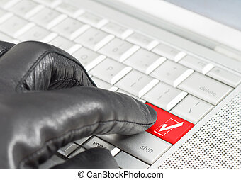 Fake online concept with hand wearing black leather glove pressing a metallic keyboard button