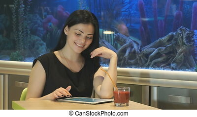 Girl looks at photos using a silver digital tablet