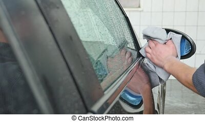 Hand wipe cleaning the car with microfiber cloth.