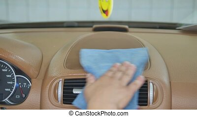 Hand cleaning interior car door panel with microfiber cloth.