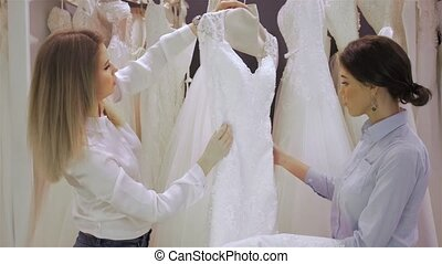 Female shop consultant helps bride chooses dress at shop of...