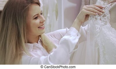 Female shop consultant helps bride chooses dress at shop of wedding fashion. Focus on girl.