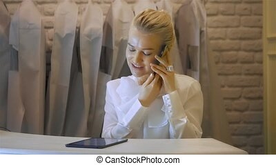 Shop assistant with phone working in clothing store. Woman...
