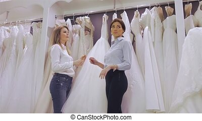 Smiling pretty bride chooses white gown at shop of wedding...