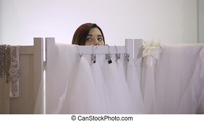 fitting wedding dress, shop asssistant helps customer.