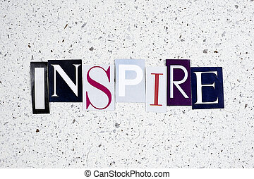 inspire word cut from newspaper on carton background