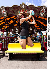 Fun girl jumping at Carousel