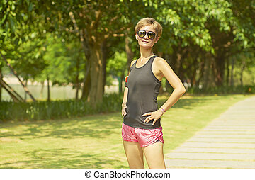 young Asian woman smiling at camera after jogging in  park