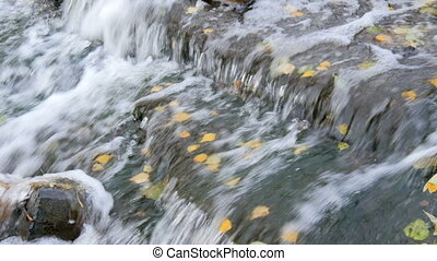 A small waterfall in autumn park. - A small waterfall in...