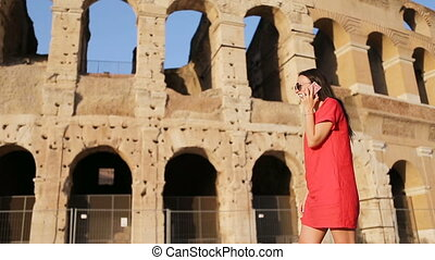 Young woman talking by smartphone in front of colosseum in...