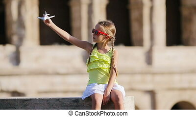 Adorable girl with small toy model airplane background...