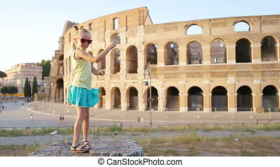 Little girl having fun in front of Colosseum in Rome, Italy....