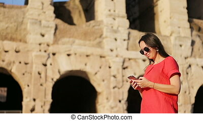Woman sending message by smartphone in front of colosseum in...