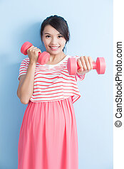 pregnant woman hold dumbell