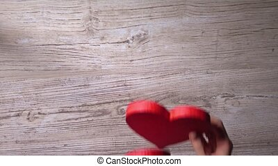 Female hands placing two red hearts on a wooden table, top...